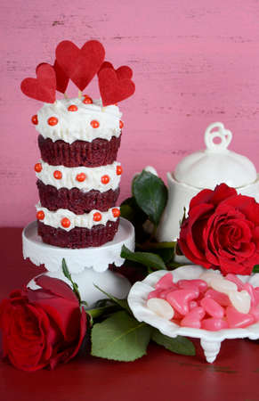 red velvet cupcake: Vintage style triple layer red velvet cupcake on white cake stand with roses and candy against a vintage shabby chic pink and red wood background. Vertical. Stock Photo