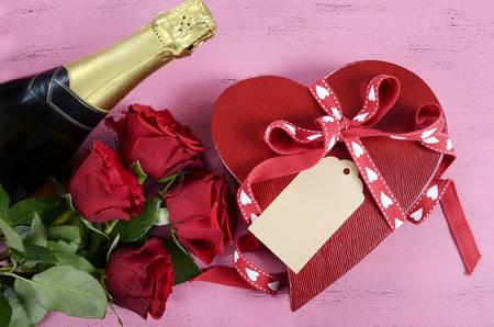 bouquet de fleurs: Bonne bo�te cadeau Saint Valentin en forme de coeur rouge avec bouteille de champagne et des roses rouges sur shabby chic style vintage bois rose fond de tableau. Banque d'images