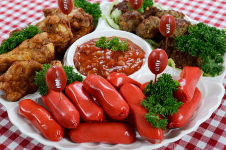 super bowl: Super Bowl Sunday football party celebration food platter with chicken buffalo wings, meat balls, hot dogs and salsa dip on red check table cloth.