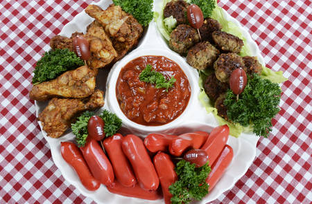 super bowl: Super Bowl Sunday football party celebration food platter with chicken buffalo wings, meat balls, hot dogs and salsa dip on red check table cloth, overhead.
