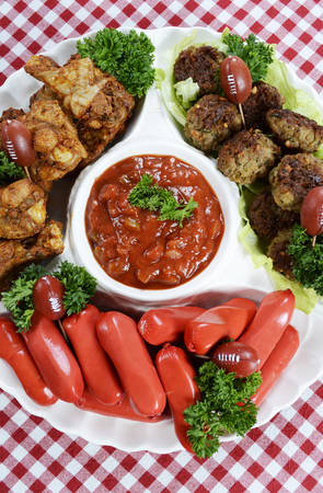 super bowl: Super Bowl Sunday football party celebration food platter with chicken buffalo wings, meat balls, hot dogs and salsa dip on red check table cloth, vertical overhead. Stock Photo