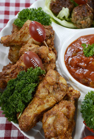 football fan: Super Bowl Sunday football party celebration food platter with chicken buffalo wings, meat balls, hot dogs and salsa dip on red check table cloth, vertical closeup on chicken wings.