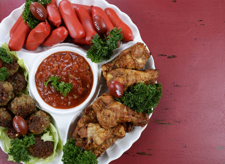 football party: Super Bowl Sunday football party celebration food platter with chicken buffalo wings, meat balls, hot dogs and salsa dip on red wood table, with copy space.