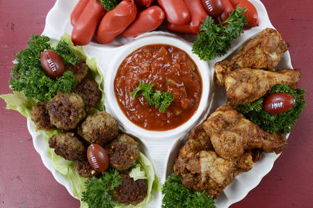 football party: Super Bowl Sunday football party celebration food platter with chicken buffalo wings, meat balls, hot dogs and salsa dip on red wood table, overhead. Stock Photo
