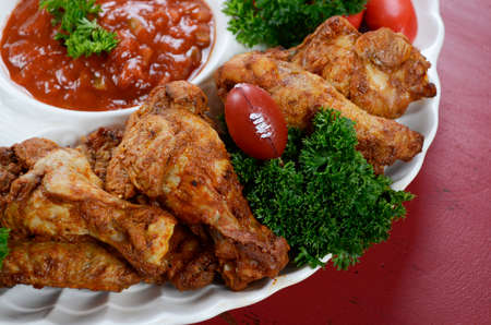 super bowl: Super Bowl Sunday football party celebration food platter with chicken buffalo wings, meat balls, hot dogs and salsa dip on red wood table.