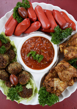 super bowl: Super Bowl Sunday football party celebration food platter with chicken buffalo wings, meat balls, hot dogs and salsa dip on red wood table, overhead vertical.