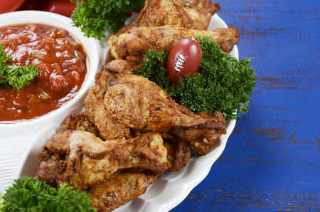party food: Super Bowl Sunday football party celebration food platter with chicken buffalo wings, meat balls, hot dogs and salsa dip on blue wood table.