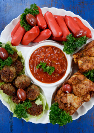 super bowl: Super Bowl Sunday football party celebration food platter with chicken buffalo wings, meat balls, hot dogs and salsa dip on blue wood table, vertical overhead. Stock Photo