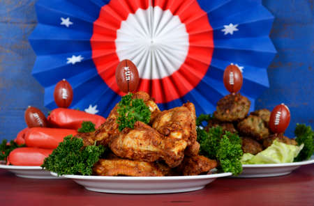super bowl: Super Bowl Sunday football party celebration food plates with chicken buffalo wings, meat balls, hot dogs and USA party decorations. Stock Photo