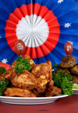 football party: Super Bowl Sunday football party celebration food plates with chicken buffalo wings, meat balls, hot dogs and USA party decorations, vertical. Stock Photo