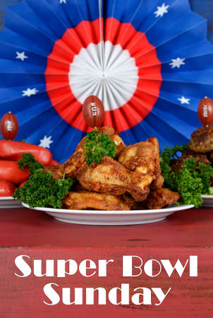 super bowl: Super Bowl Sunday football party celebration food plates with chicken buffalo wings, meat balls, hot dogs and USA party decorations, with text, vertical.