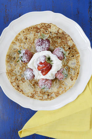 shrove: Shrove Pancake Tuesday pancakes with strawberries and cream on dark blue vintage shabby chic table, vertical. Stock Photo