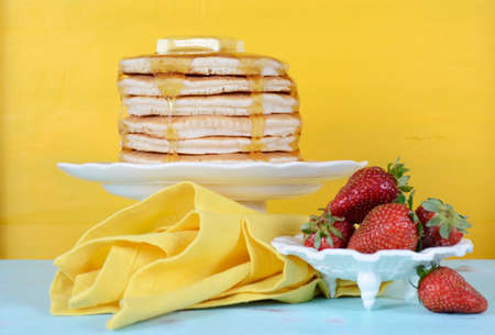 shrove tuesday: Shrove Pancake Tuesday stack of pancakes with honey and butter and strawberries on yellow and aqua blue vintage shabby chic table. Stock Photo