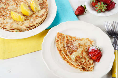 shrove: Shrove Pancake Tuesday pancakes with lemons and strawberries with yellow and blue napkins on white vintage shabby chic table.