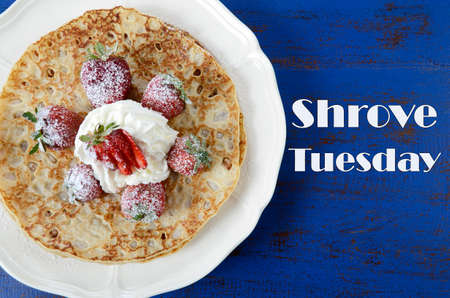 shrove: Shrove Pancake Tuesday pancakes with strawberries and cream on dark blue vintage shabby chic table, and text.