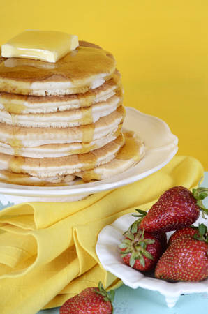 shrove: Shrove Pancake Tuesday stack of pancakes with honey and butter on yellow and aqua blue vintage shabby chic table, vertical with strawberries. Stock Photo