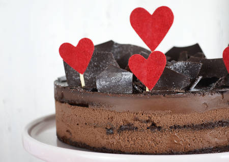 shards: Valentine chocolate mousse layer gateau cake with chocolate shards decoration and red hearts on shabby chic vintage white and pink wood background. Stock Photo