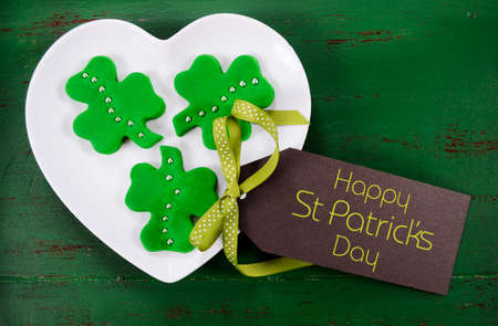 Happy St Patricks Day shamrock shape green fondant cookies on white heart shape plate on vintage style green wood table. photo