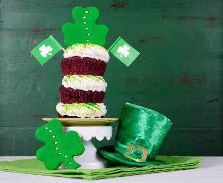 Happy St Patricks Day triple layer cupcake with shamrock decorations and leprechaun hat against a vintage style green wood background.