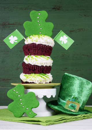 layer style: Happy St Patricks Day triple layer cupcake with shamrock decorations and leprechaun hat against a vintage style green wood background.