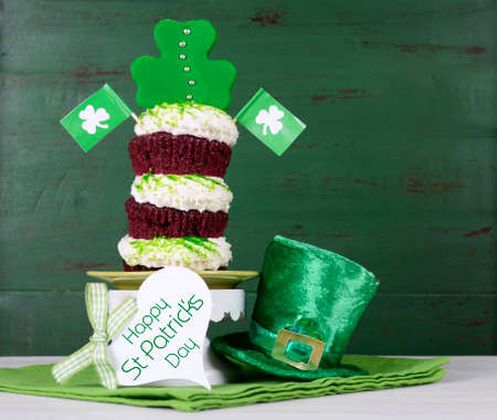leprechaun: Happy St Patricks Day triple layer cupcake with shamrock decorations and leprechaun hat against a vintage style green wood background.
