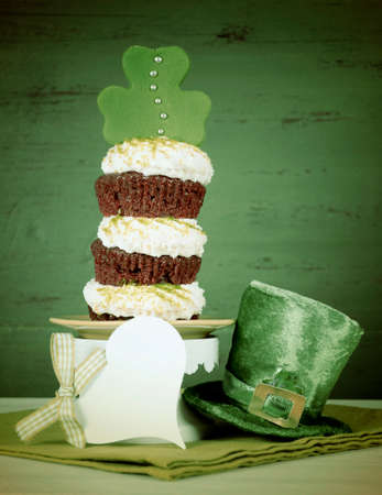 layer style: Happy St Patricks Day triple layer cupcake with shamrock decorations and leprechaun hat against a vintage style green wood background, with added retro vintage style filters.