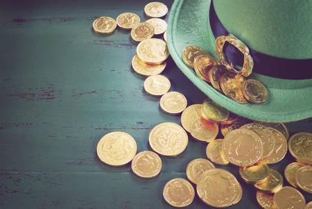 monedas antiguas: Feliz sombrero de duende Día de San Patricio con monedas de chocolate de oro en estilo vintage fondo de madera verde, con filtros de estilo retro vintage.
