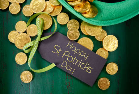 Happy St Patricks Day leprechaun hat with gold chocolate coins on vintage style green wood background.