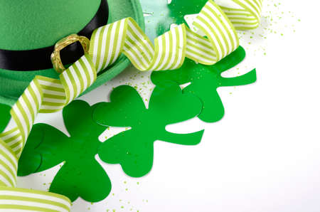 march 17: Happy St Patricks Day leprechaun hat with shamrocks and party ribbons on white table.