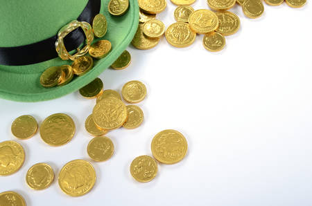 gold holidays: Happy St Patricks Day leprechaun hat gold chocolate coins on white table.