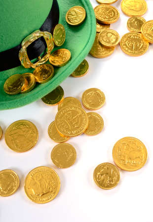 leprechaun background: Happy St Patricks Day leprechaun hat gold chocolate coins on white table.