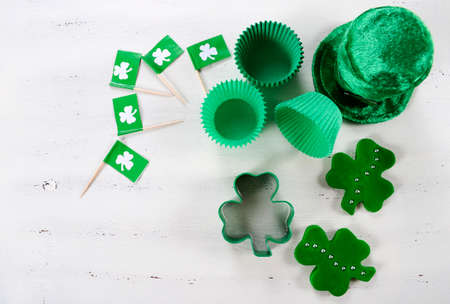 Happy St Patricks Day cooking and baking concept with green cupcake pans and shamrock cookie cutter  on vintage style white wood table. photo