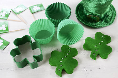 cookie cutter: Happy St Patricks Day cooking and baking concept with green cupcake pans and shamrock cookie cutter  on vintage style white wood table.