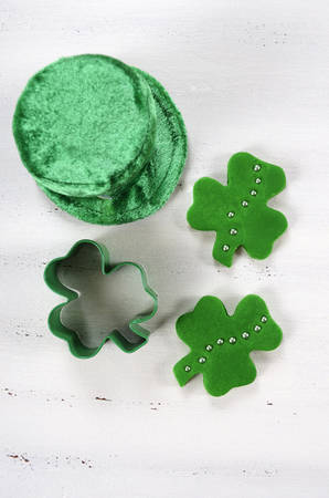 Happy St Patricks Day cooking and baking concept with green cupcake pans and shamrock cookie cutter  on vintage style white wood table.
