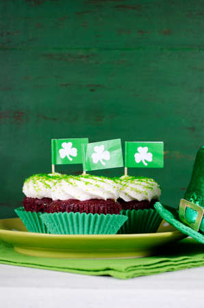 Happy St Patricks Day cupcakes with green theme decorations on vintage style green wood background. Stock Photo