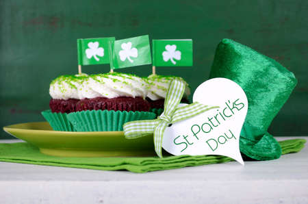 Happy St Patricks Day cupcakes with green theme decorations on vintage style green wood background. Imagens