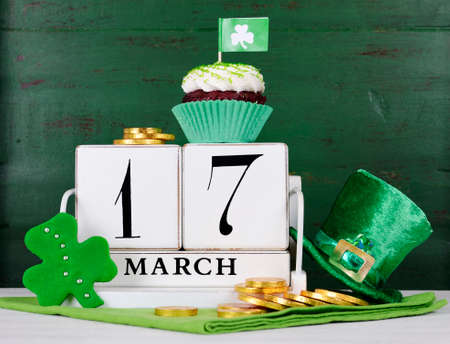 white day: Happy St Patricks Day save the date white vintage wood calendar with cupcakes on vintage style green wood background. Stock Photo