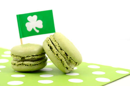 shamrock: Happy St Patricks Day green macaron cookies with shamrock flag on white table.