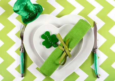 leprechaun on clover: Happy St Patricks Day table place setting with heart shape plates, shamrock cookie and leprechaun hat on green and white chevron stripe table.
