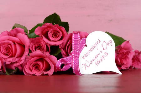 womens day: International Womens Day, March 8, pink roses with gift tag message on vintage pink wood background. Stock Photo