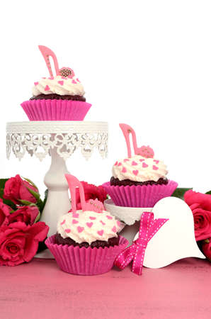 International Womens Day, March 8, cupcakes with high heel stiletto fondant shoes on cake stands on vintage pink wood and white background, vertical. photo