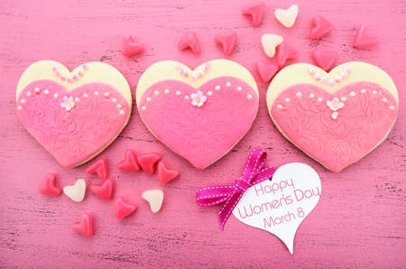 International Womens Day, March 8, heart shape cookies decorated as pink ladies dresses on vintage pink wood background. photo