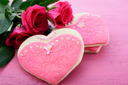International Womens Day, March 8, heart shape cookies decorated as pink ladies dresses with bouquet of pink roses on vintage pink wood background, closeup. photo