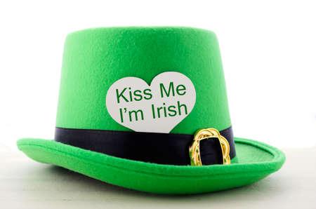 leprechaun: Happy St Patricks Day green leprechaun hat on white wood table with Kiss Me I am Irish heart shape greeting sign. Stock Photo