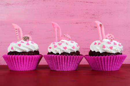 Día Internacional de la Mujer, 8 de marzo de magdalenas con los zapatos de tacón de aguja de pasta de azúcar en el fondo de madera de época de color rosa. Foto de archivo - 36571165