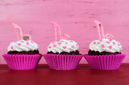 International Womens Day, March 8, cupcakes with high heel stiletto fondant shoes on vintage pink wood background. photo