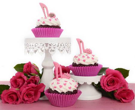 Día de la Mujer Internacional, 8 de marzo de magdalenas con los zapatos de tacón de aguja en la torta de la pasta de azúcar se encuentra en la madera de color rosa vintage y fondo blanco. Foto de archivo - 36571169