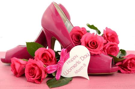 Festa della donna, l'8 marzo, le donne rosa scarpe tacco alto a spillo e le rose su sfondo di legno rosa vintage, con la modifica di auguri a forma di cuore. Archivio Fotografico - 36571170