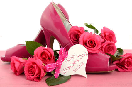 International Womens Day, March 8, ladies pink high heel stiletto shoes and roses on vintage pink wood background, with heart shape greeting tag.