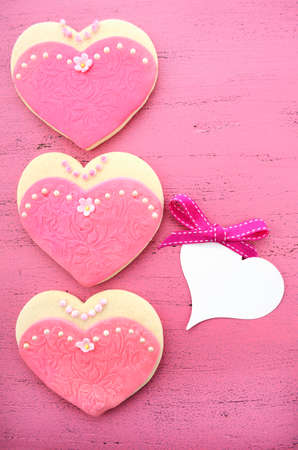International Womens Day, March 8, heart shape cookies decorated as pink ladies dresses on vintage pink wood background, vintage. photo